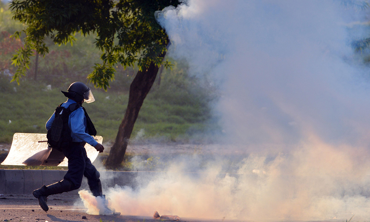 A Pakistani riot policeman kicks a tear gas shell - AFP