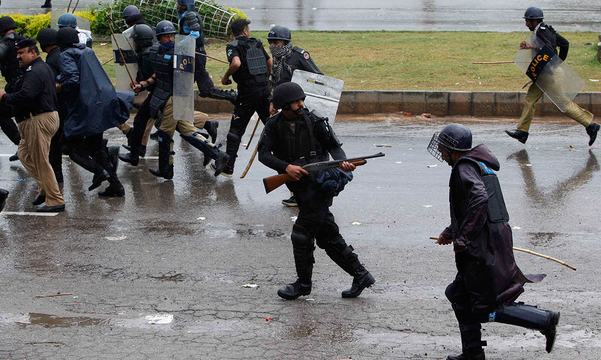 A policeman fires his weapon as he runs away with others from supporters of Tahirul Qadri during the march towards the prime minister's house in Islamabad, Sept 1, 2014. — Reuters