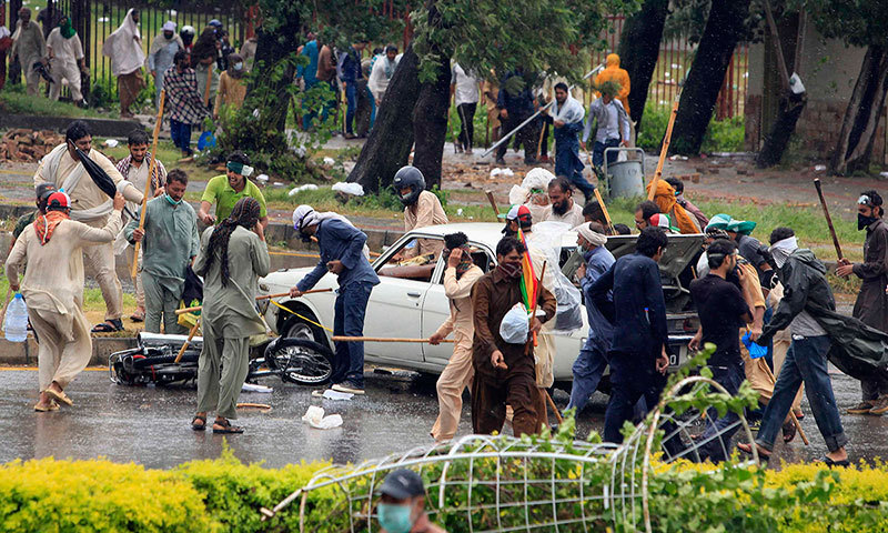 Supporters of Tahirul Qadri use sticks to hit a car and a motorcycle as they protest during a march towards the prime minister