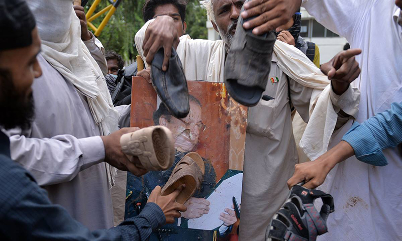 Protesters hit a poster bearing the image of PM Nawaz with shoes after storming the headquarters of PTV. — Photo by AFP