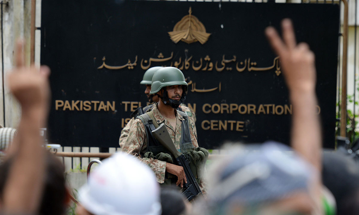 Soldiers stand guard outside the headquarters of PTV after the building was stormed by supporters of Tahirul Qadri and Imran Khan during anti-government protests in Islamabad on September 1, 2014. — AFP
