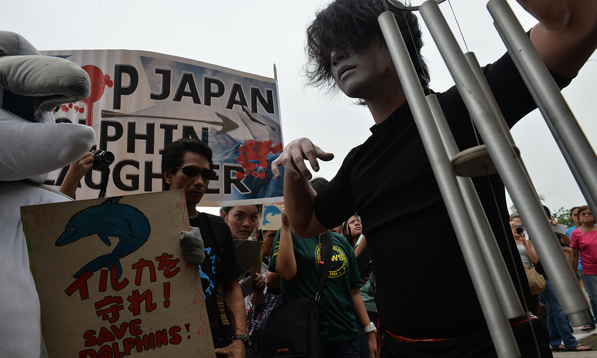 A Filipino activist performs a street play during a protest at the Japanese embassy. AFP