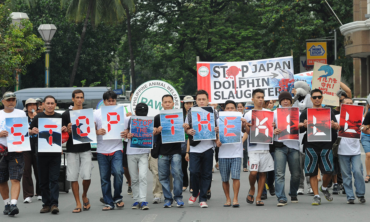 """Filipino activists holding slogan-placards """"stop the kill"""" march towards the Japanese embassy. AFP"""