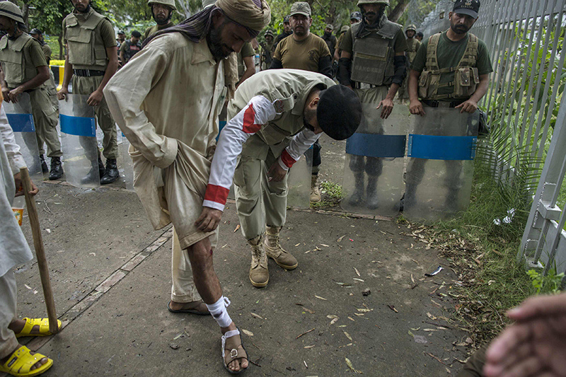 Army medic checks the injury of a supporter of Tahir ul-Qadri — Reuters Photo