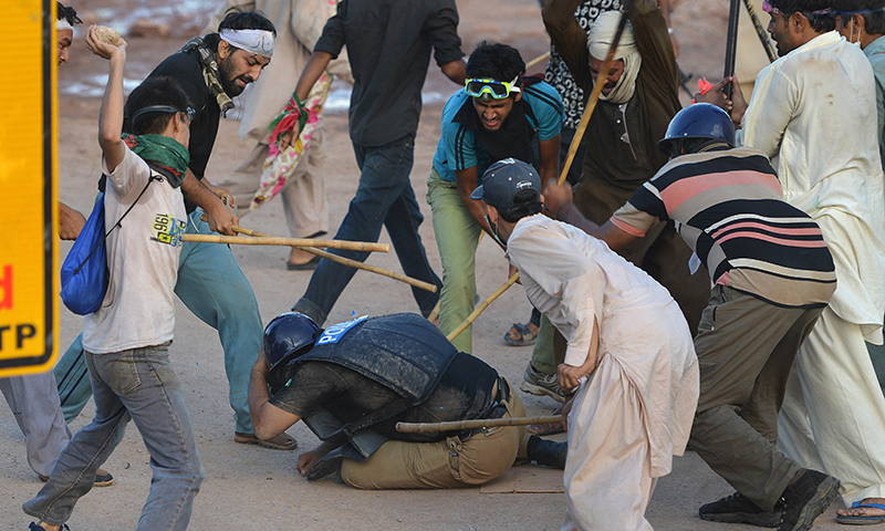 Supporters of cricketer-turned politician Imran Khan and Canadian cleric Tahir ul Qadri beat a riot policeman during an anti-government protest in Islamabad on September 1, 2014 — AFP