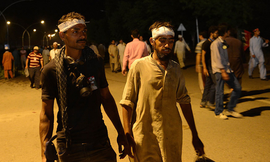 Injured opposition protesters walk during the anti-government march near the prime minister's residence in Islamabad on September 1, 2014. – AFP Photo