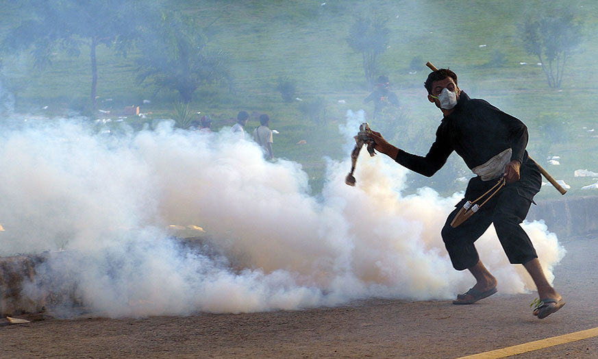 A supporter of Canadian cleric Tahirul Qadri returns a tear gas shell towards riot police during an anti-government protest in Islamabad on September 1, 2014. – AFP Photo