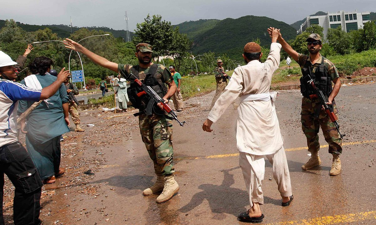 A supporter (2nd R) of Tahirul Qadri lifts up the hand of a Pakistan Army soldier during a march towards the prime minister's house in Islamabad, September 1, 2014. — Photo by Reuters