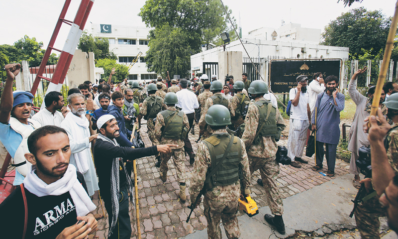 Islamabad: Troops arrive to clear the PTV building occupied by protesters here on Monday.—AP