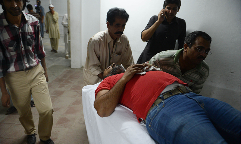 Paramedics move an injured journalist at a hospital after clashes in Islamabad. Photo by AFP