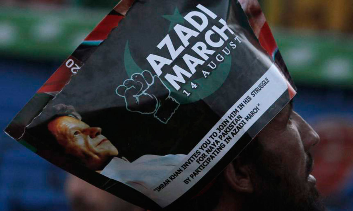 A supporter of chairman of the Pakistan Tehreek-e-Insaf (PTI) political party Imran Khan wears a poster on his head as he listens to his speech a Freedom March in Islamabad. – Photo by Reuters