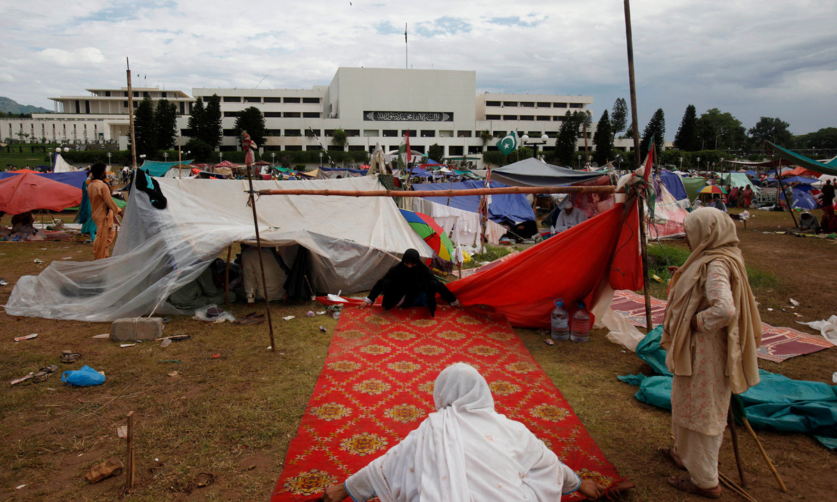 Women supporters of Tahirul Qadri arrange their makeshift camp in front of the parliament building in Islamabad. - Photo by AP