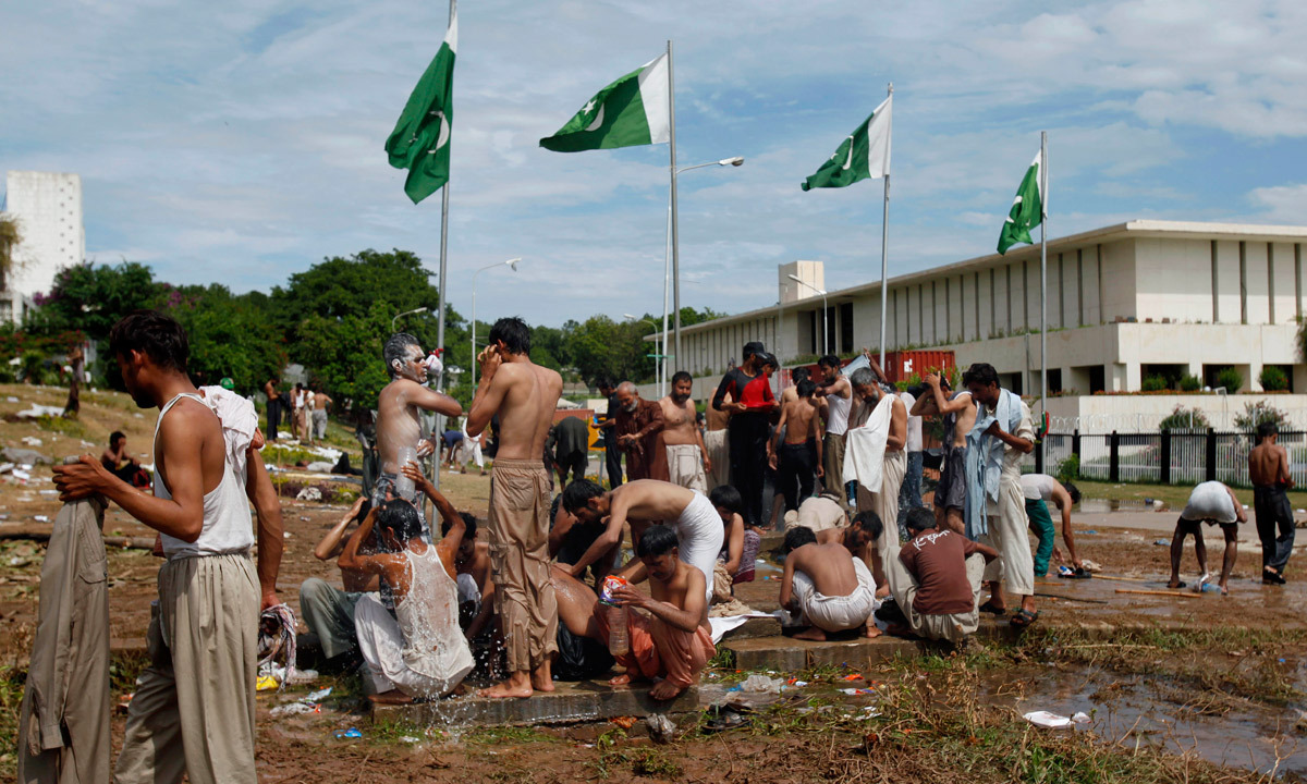 Protesters bathe at a leaking water supply line close to the parliament building where they are camped in Islamabad. - Photo by AP