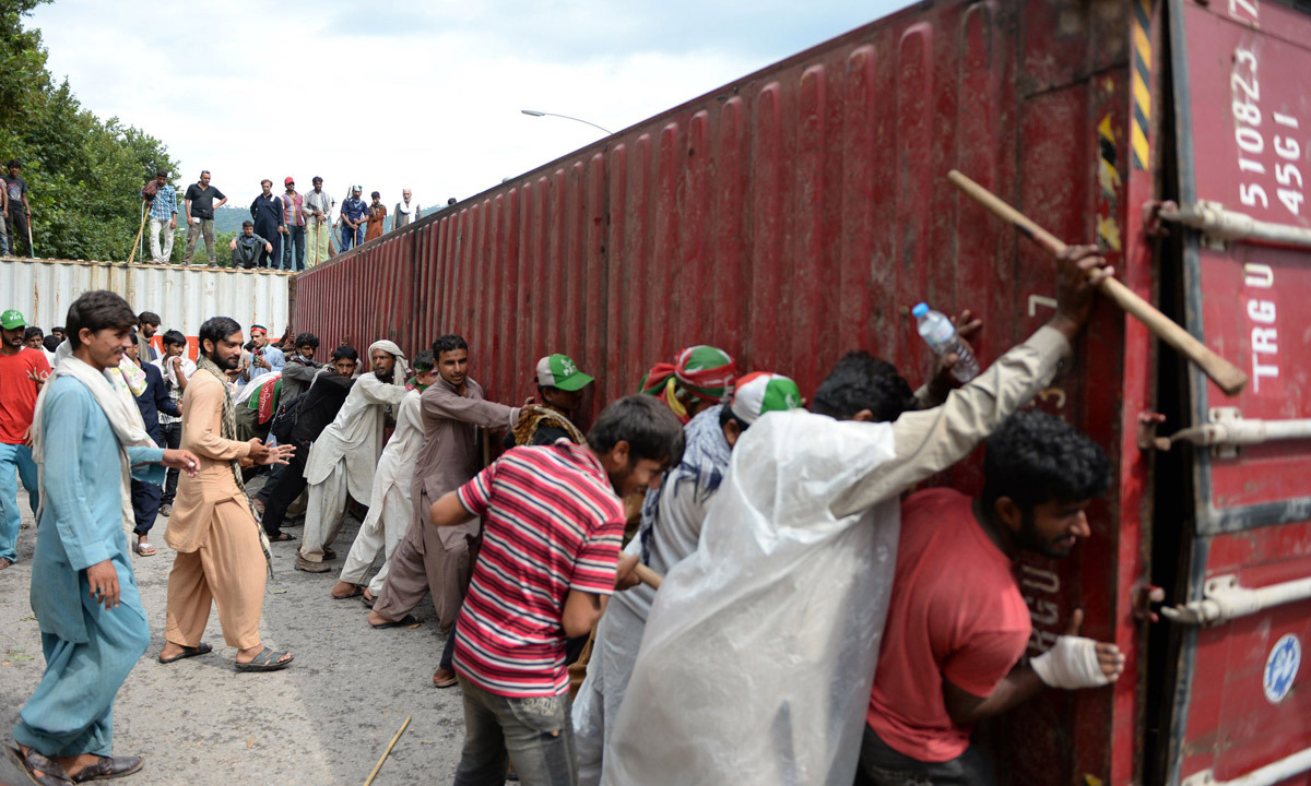 Supporters of  Imran Khan and Tahirul Qadri remove a container during an anti-government protest near the parliament building in Islamabad. - Photo by AFP