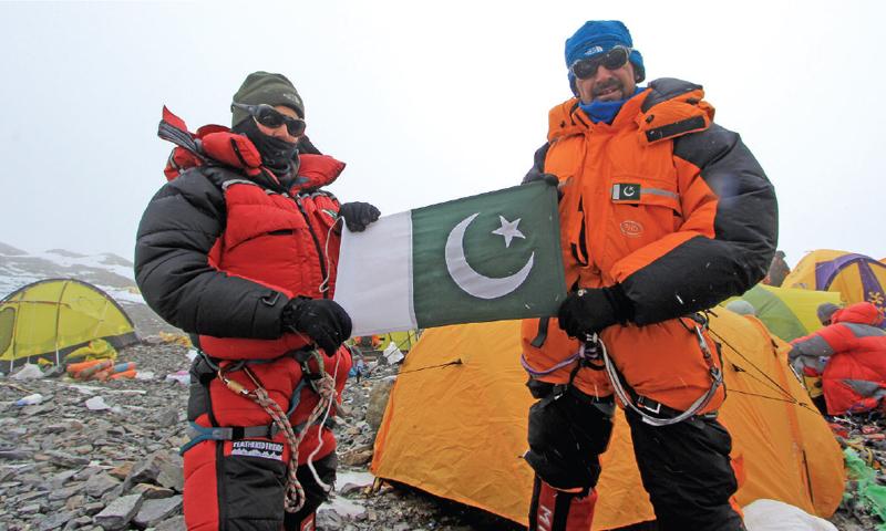 Samina Baig (L) and Mirza Ali Baig (R) pose with the Pakistani flag at Mount Everest.
