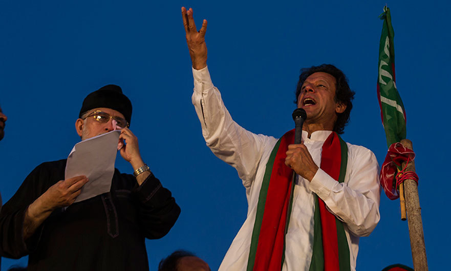 Imran Khan addresses supporters while flanked by Tahirul Qadri in Islamabad. -Reuters Photo
