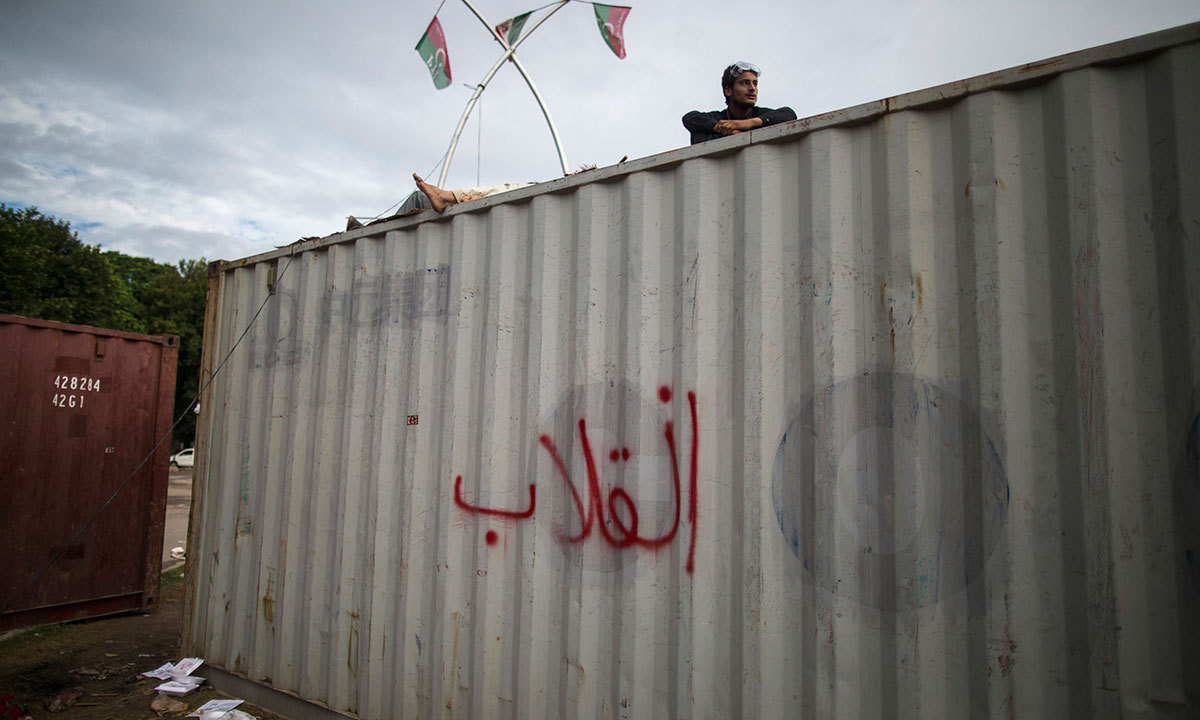 An anti-government protester sits atop a container while his fellow protester sleeps, in front of the President House, Islamabad, Sept 3, 2014. — Photo by Reuters