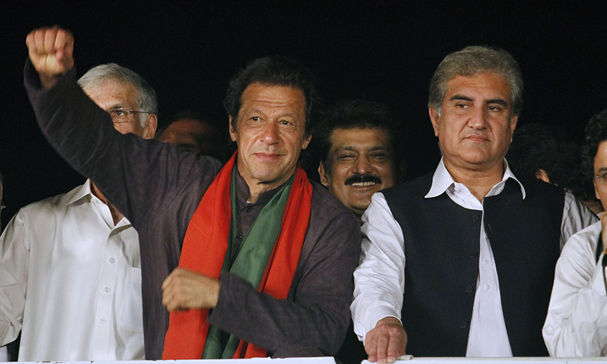 Imran Khan, left, raises his arm before his supporters as his party leader Shah Mahmood Qureshi, right, looks on during a protest in Islamabad, Pakistan, Wednesday, Sept. 3, 2014.— AP Photo