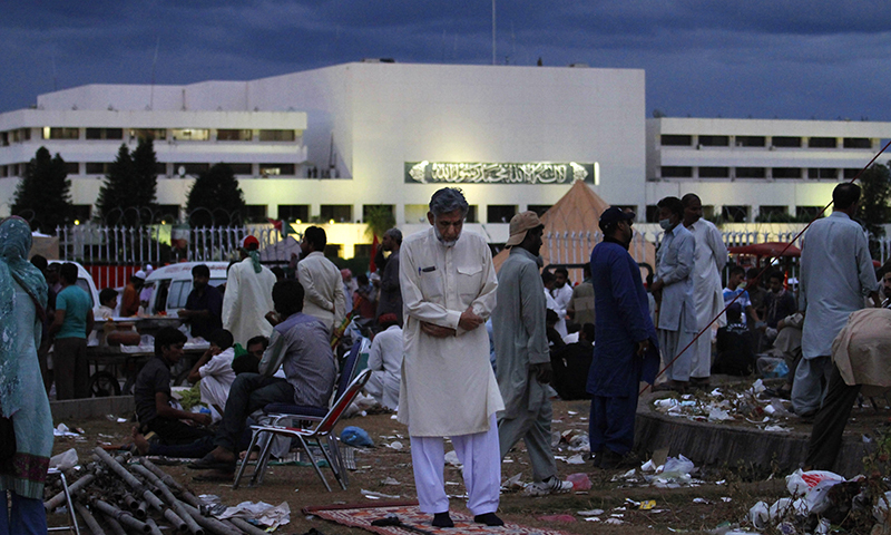 Protester offers evening prayers as others occupied a roundabout in front of parliament building, background — AP photo