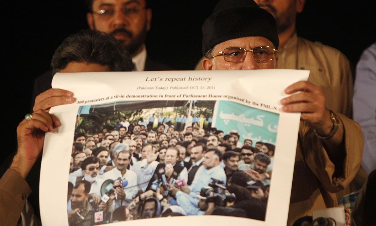 Tahirul Qadri (R, front) displays a newspaper cutting with a picture of a sit-in protest by Nawaz Sharif and supporters published on October 13, 2011, during the Revolution March in Islamabad September 3, 2014. — Photo by Reuters