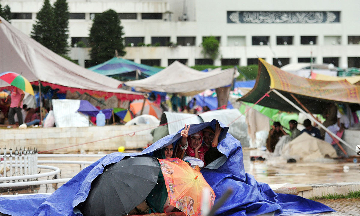 Supporters of Tahirul Qadri take cover under plastic sheeting during heavy rain on the lawn of the Parliament premises during an anti-government protest in Islamabad on September 4, 2014. — AFP