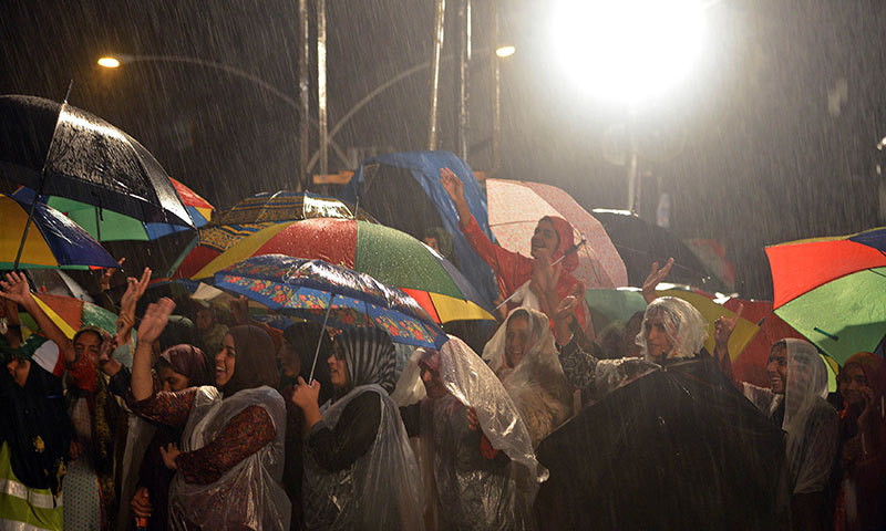 Supporters of Dr Tahirul Qadri cheer as they listen to Qadri's speech while heavy rains fall during an anti-government protest near the PM House in Islamabad on September 4, 2014. – AFP Photo