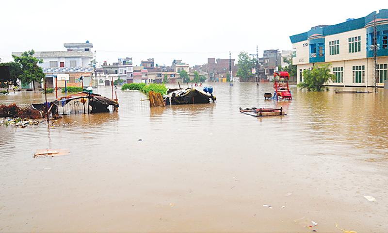 LAHORE: Rainwater inundates the China Scheme locality here on Thursday.—M. Arif / White Star