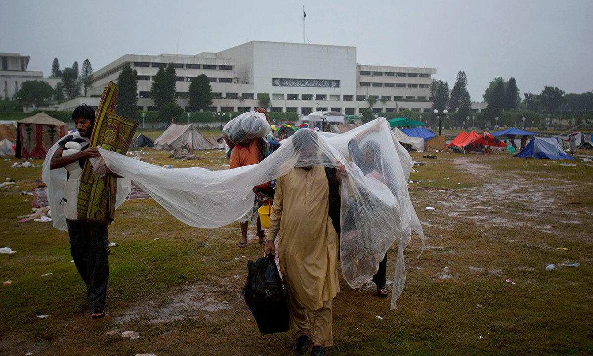 Protesters use plastic sheet to cover themselves from rain as they move to another place at the premises of Parliament building where they camped in Islamabad, Sept 4, 2014. — AP