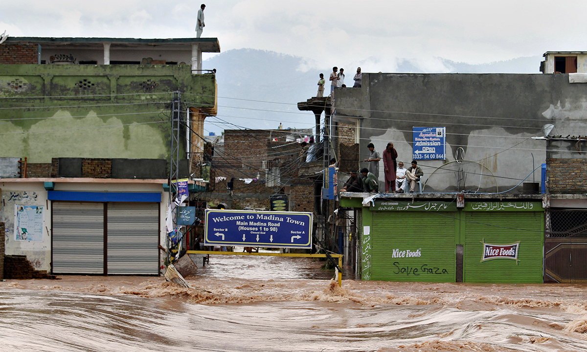 People stand on the rooftop of their flooded houses caused by heavy rains on the outskirts of Islamabad, Pakistan, Friday, Sept. 5, 2014. Heavy monsoon rains killed dozens of people across Pakistan as flash flooding inundated villages, prompting authorities to send troops to evacuate residents and assist in the emergency, officials said. (AP Photo/Anjum Naveed)
