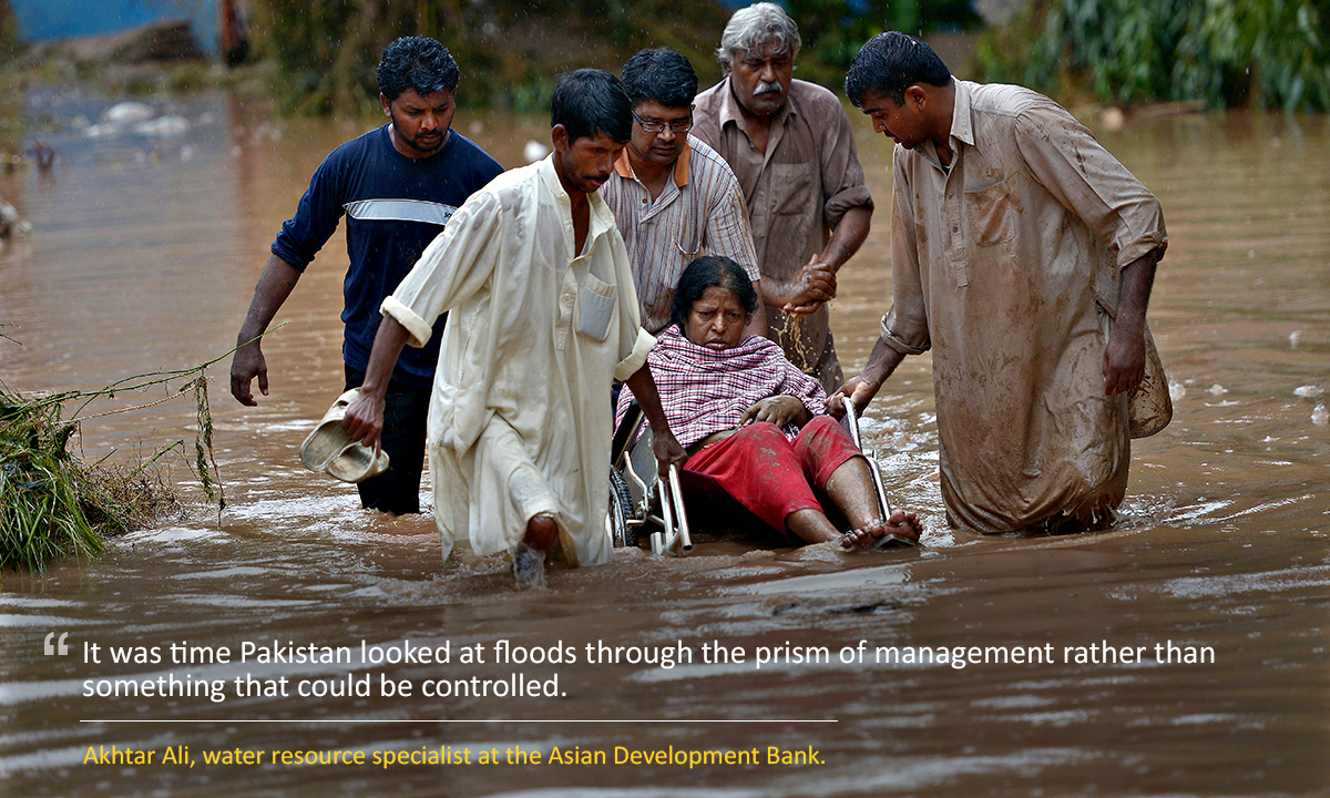 Pakistani Christians assist an elderly woman in the flooded area of Rawalpindi on September 5, 2014.  Two days of torrential monsoon rains have killed nearly 70 people in Pakistan, officials said September 5, as authorities ordered the evacuation of low-lying areas around a major river.   AFP PHOTO/Farooq NAEEM