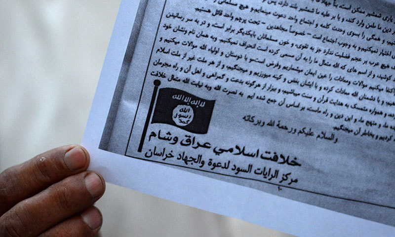 This photograph taken on September 3, 2014 shows a Pakistani man holding a pamphlet, allegedly distributed by the Islamic State (IS), in Peshawar. – AFP Photo