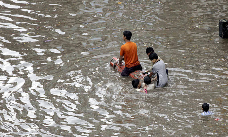 Youngsters crossing the flooded Lakshami Chowk on LPG cylinder after heavy rain. — Photo by INP