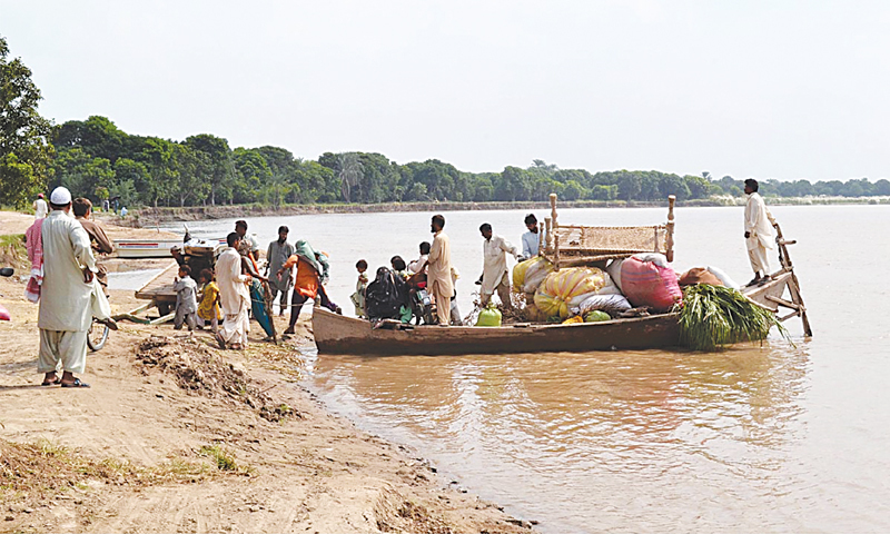 MULTAN: People affected by rains use a boat to move to safe areas as the Chenab river rose to dangerously high levels on Saturday.—Online