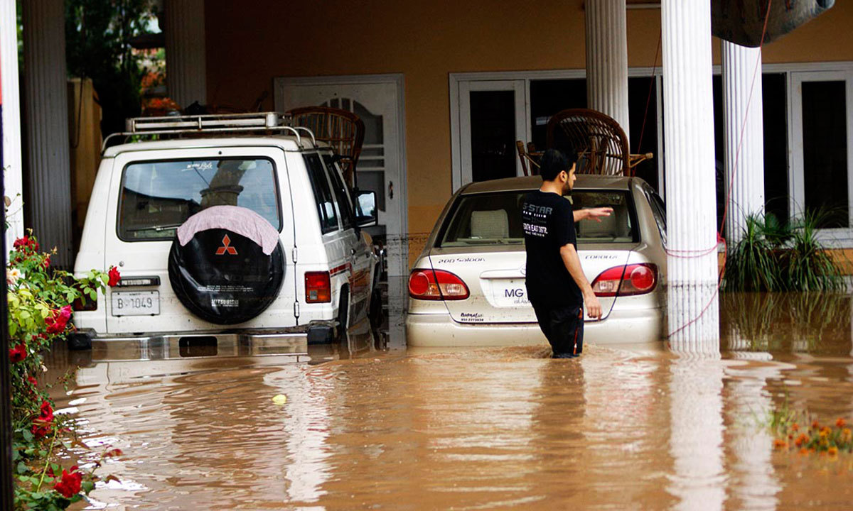 A Pakistani family stands inside their house following flooding in Rawalpindi. — Photo by Online
