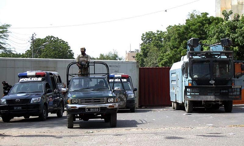 Rangers and police personnel seen in front of containers placed to block road in Karachi. — Photo by Online