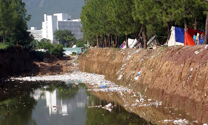 A view of rain water and garbage in metro bus way near the tents of PAT protests causing  health problems for people in the area. — Photo by INP