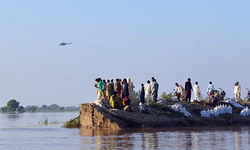 Villagers gather on higher ground as floodwaters enter in the Hafizabad district in Punjab province on September 8, 2014.— Photo by AFP