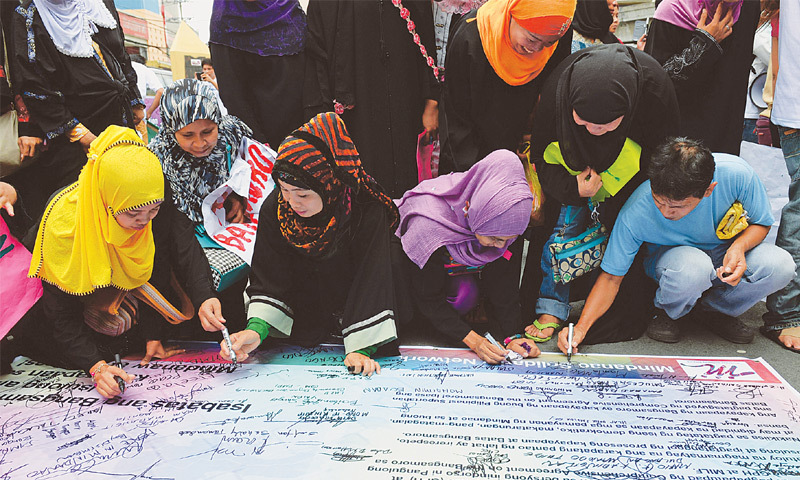 Manila: Muslims sign a placard during a rally near the Malacanang Palace on Wednesday in support of a law giving autonomy to the community.—AFP