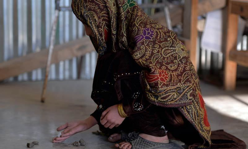 In this photograph taken on Dec 12, 2013, young Pakistani girl Saneeda, who escaped a forced marriage under a local custom of Swara, plays a local game in the Madyan valley of Swat, in the country's northwest. — AFP