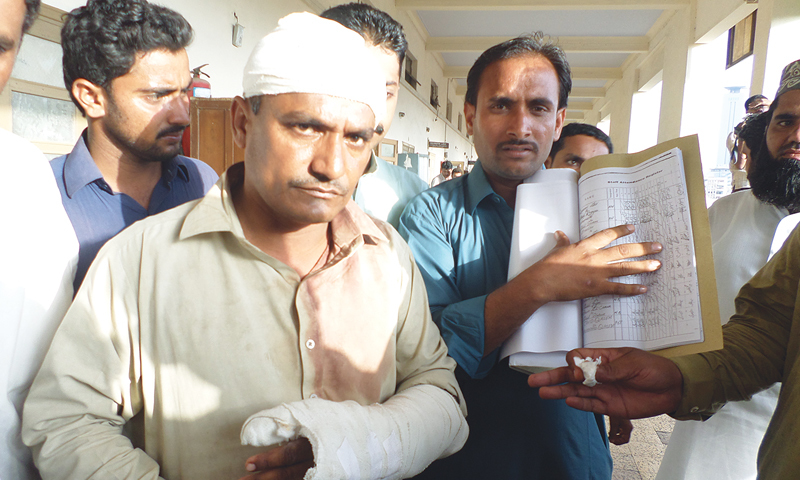 Injured Sindhi language teacher Niaz Ahmed at the City Court with his colleague Ali Gauhar showing the proof of their appointments by the Sindh Education Department two years ago.—Photo by writer.