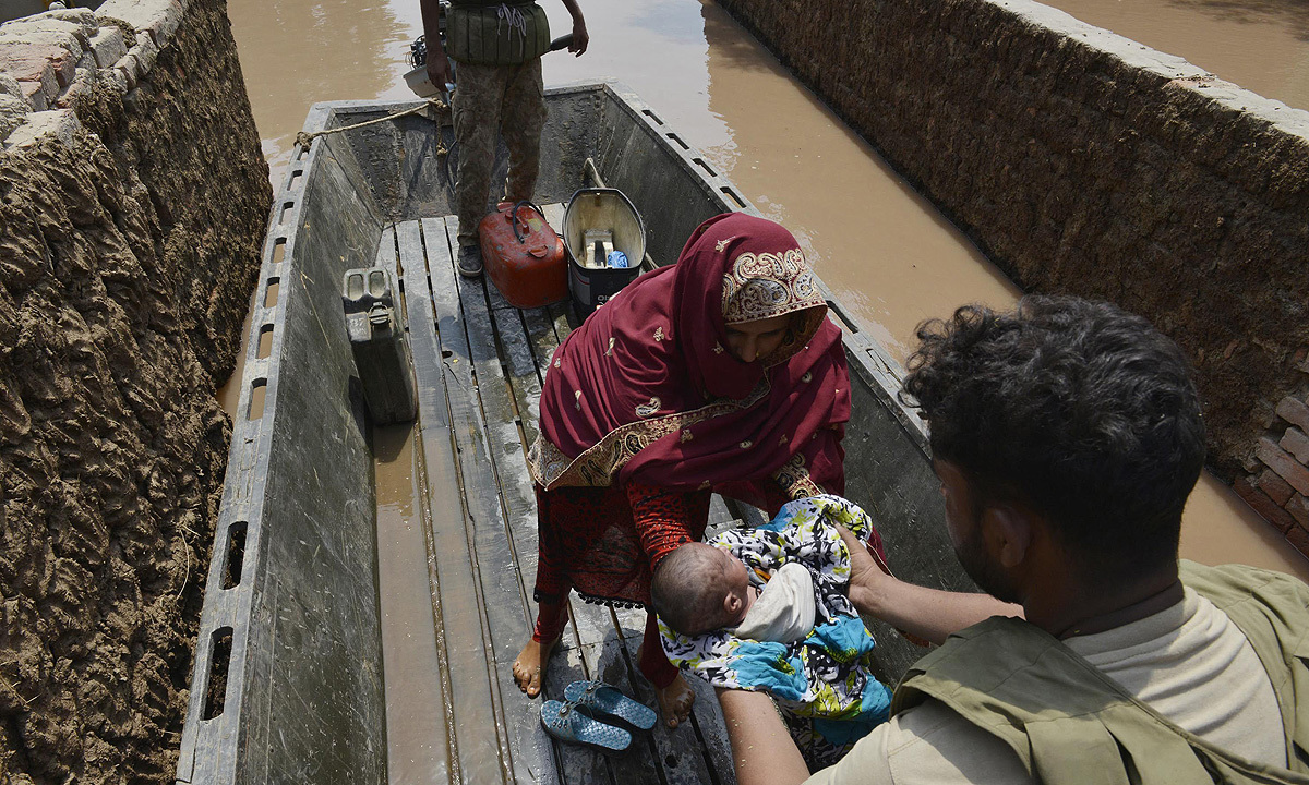 A soldier helps a child and mother who were rescued from a flood-affected area in Sher Shah, a town in Multan District. -Photo by AFP