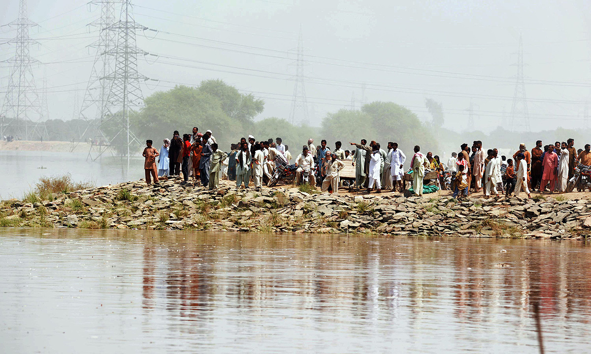 Residents affected by flooding gather with their belongings on high ground in Sher Shah, a town in Multan District. -Photo by AFP