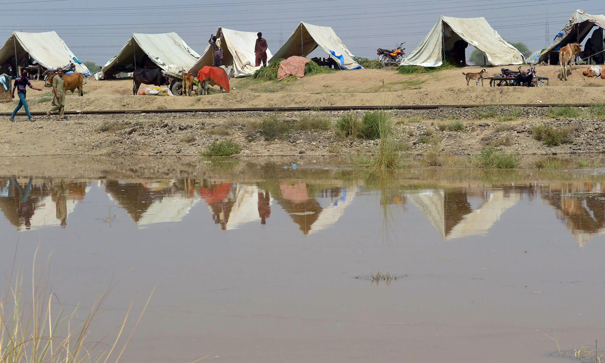 Residents affected by flooding sit inside their tents on high ground in Sher Shah, a town in Multan District. -Photo by AFP