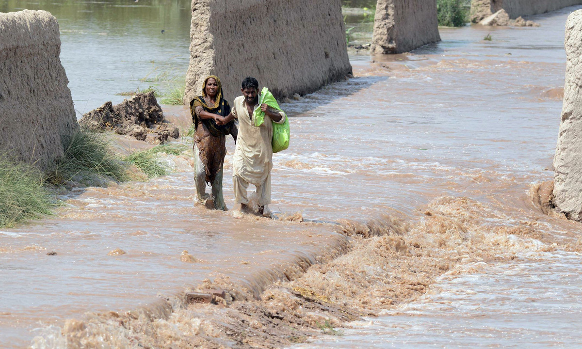 Residents wade through floodwater in Sher Shah, a town in Multan District. -Photo by AFP
