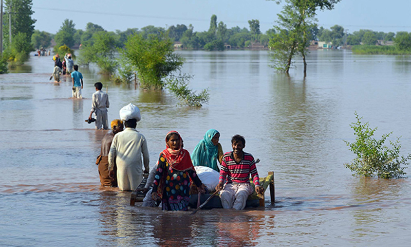 Pakistani residents wade through floodwaters at a village in Jhang. — File photo/AFP