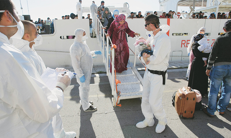 Women disembark from a boat at the Brindisi harbour, southern Italy, following rescue operations at sea. According to the Italian navy, some 2,380 migrants and asylum seekers were picked up over the weekend.—AFP