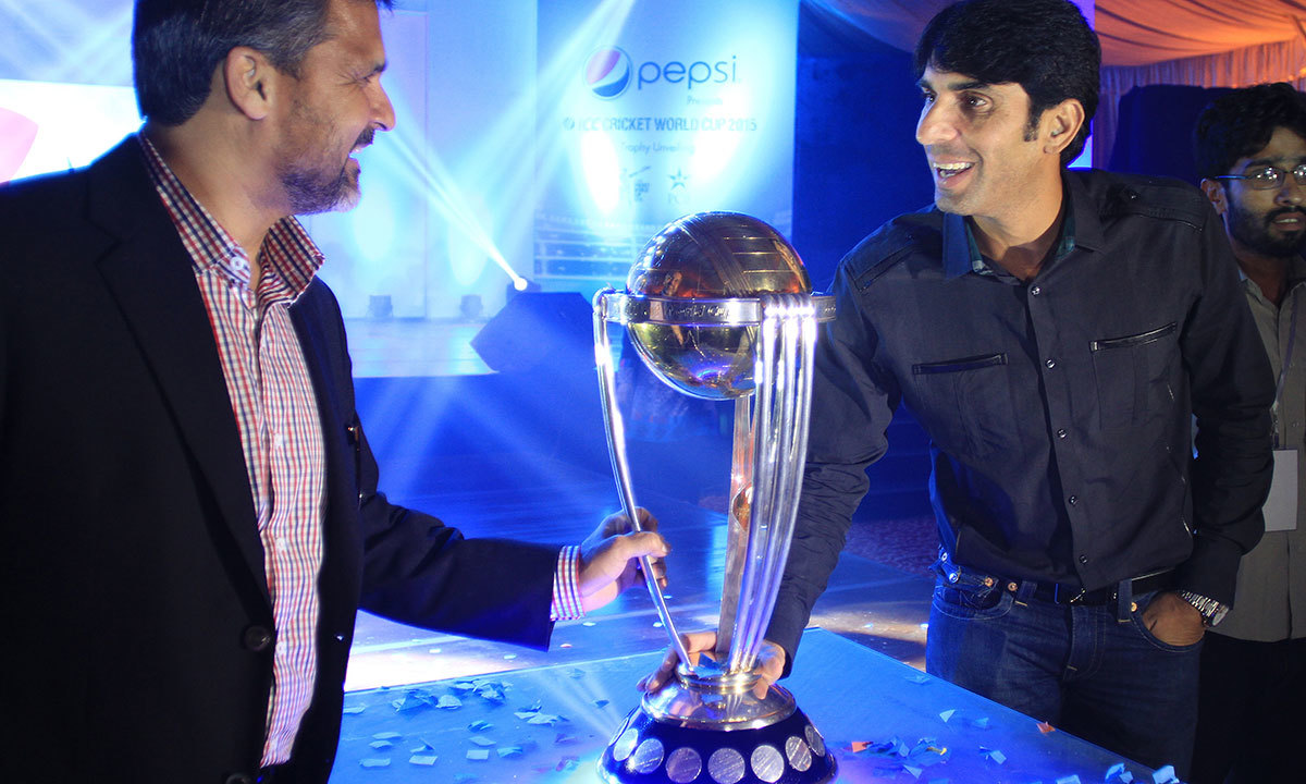 Pakistan cricket board chief selector Moin Khan, left, holds the World Cup 2015 trophy, as a part of its global tour, with cricketer Misbah-ul-Haq in Lahore. — Photo by AP