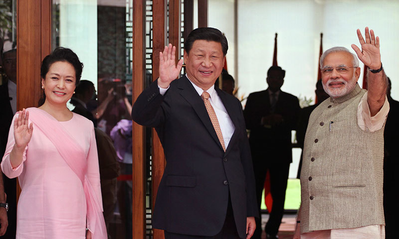 Indian Prime Minister Narendra Modi, right, Chinese President Xi Jinping and Xi's wife Peng Liyuan, left wave to the media after Modi received them upon arrival at a hotel in Ahmadabad, India, Wednesday, Sept. 17, 2014.