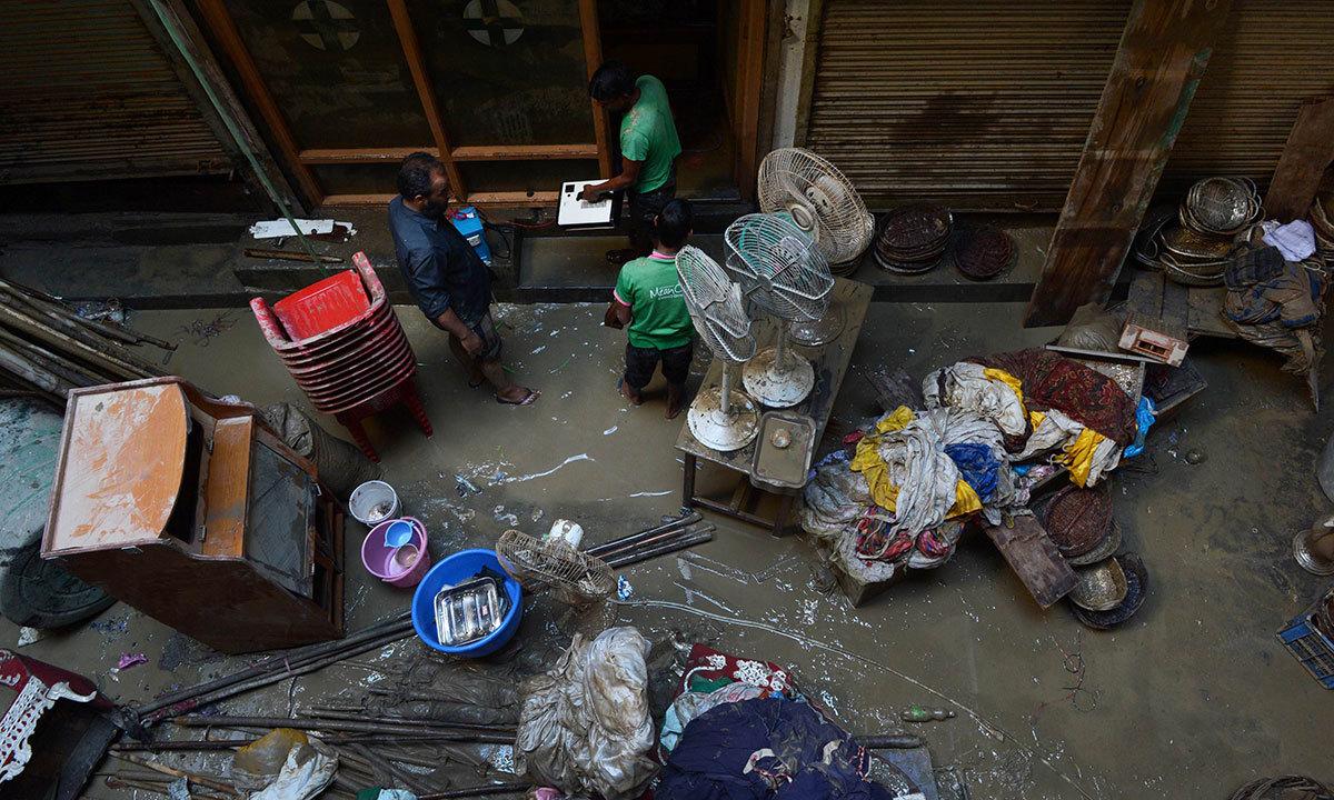 Kashmiri residents clean a flood-damaged shop in central Srinagar on September 19, 2014.  — Photo by AFP