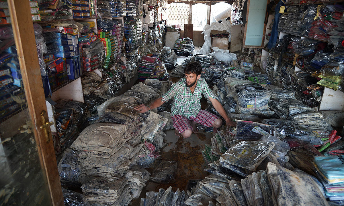 A Kashimri worker of a ready-made garment shop sorts out flood-damaged stock inside the shop in Srinagar on September 18, 2014.  — Photo by AFP